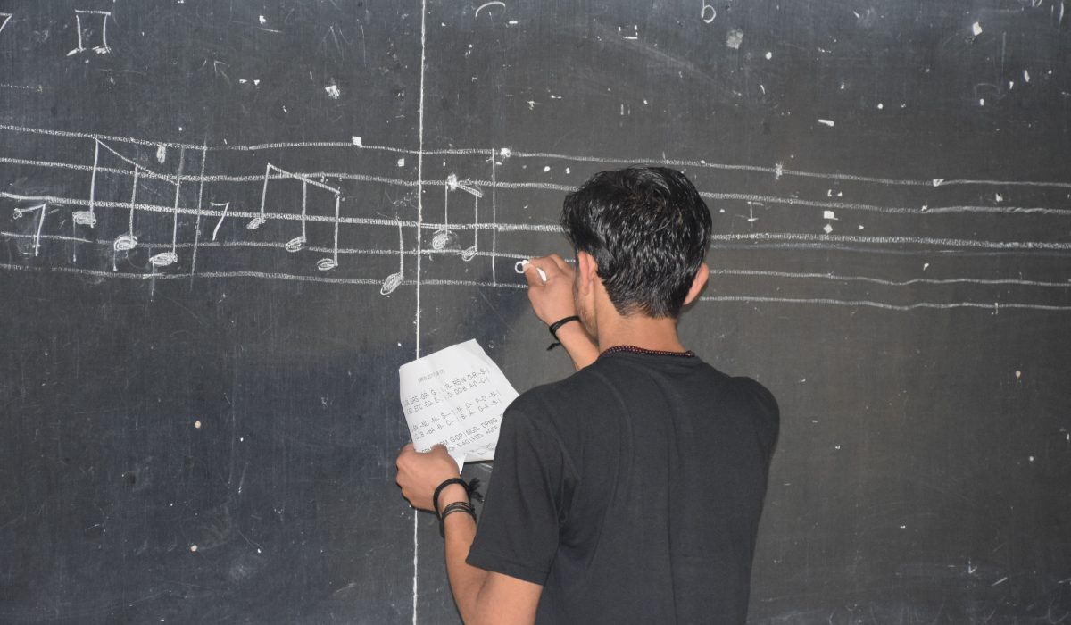 Student writing on the black board at the South Asia Global Music Campus