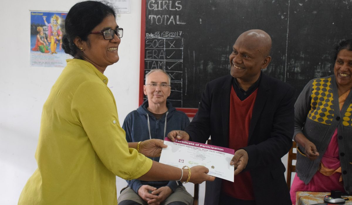 A woman receiving the certificate of participation from the South Asian Global Music Campus